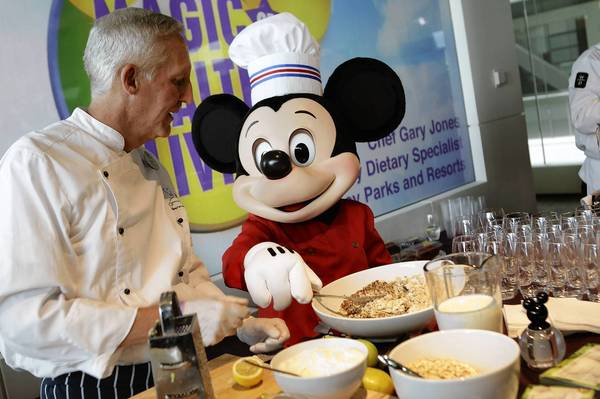 "A Mickey Mouse character helps Walt Disney Parks and Resorts culinary dietary specialist Gary Jones make healthy smoothies during an event Tuesday introducing Disney's ""Magic of Healthy Living"" program at the Newseum in Washington. As part of the new healthy eating initiative, all products advertised on Disney's child-focused television channels, radio stations and websites must adhere to a new set of strict nutritional standards."