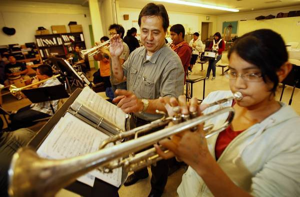 Belmont High School band director Brian Higa works with trumpeter Mayra Torres during Pep Band rehearsal at Belmont High School near downtown Los Angeles. The music program Higa has developed is scheduled to be eliminated.