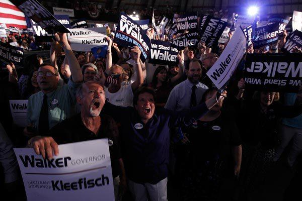 Supporters of Wisconsin Gov. Scott Walker react to a televised report that Walker is projected to be the winner in the recall election.