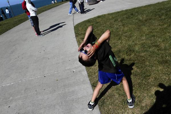 Bodhi Coffee, 8, of Oak Park, wears solar viewing glasses to see the transit of Venus on Tuesday at the Adler Planetarium in Chicago.