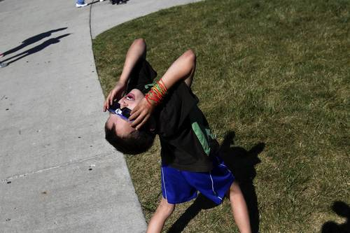 Bodhi Coffee of Oak Park bends backwards while wearing glasses made for solar viewing as the 8-year old looks toward the sun during a free public observation of the transit of Venus at the Adler Planetarium in Chicago.