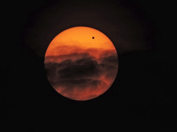 Venus, black dot upper right, moves across the face of the sun as clouds drift by. The rare astronomical event was photographed from the roof of the Maryland Science Center.