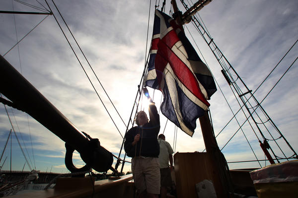 Godspeed crew member Keith Joseph of Newport News hoists the Union Jack during preparations to depart downtown Hampton for participation in Opsail Wednesday.