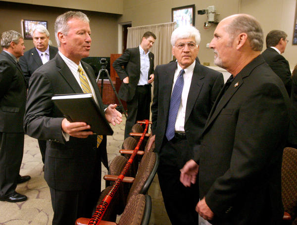 Orlando mayor Buddy Dyer chats with developer Jim Pugh (center) and former Florida Citrus Sports president Ford Kiene (right) about the future of the Florida Citrus Bowl renovations, during a public meeting at the Orange County Commission chambers in downtown Orlando,  Wednesday, June 6, 2012.