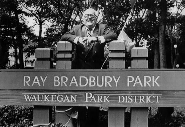 "Author Ray Bradbury leans against the sign of a park newly named in his honor on Tuesday, June 27, 1990 in Waukegan, Ill. He played at the park as a child and later wrote about it in his 1957 book ""Dandelion Wine."""