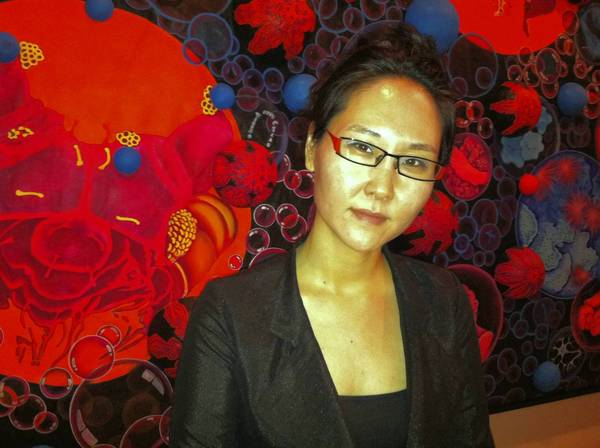 "Mina Cheon in front of her 72 x 8 feet painting ""15 Billion Years of the Traveling Atom,"" currently on view at Maryland Art Place"