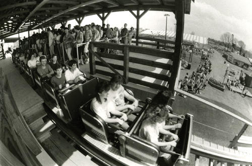People ride the roller coaster, 'Hercules' as it takes off while a long line of people wait to ride. Taken May 1989.