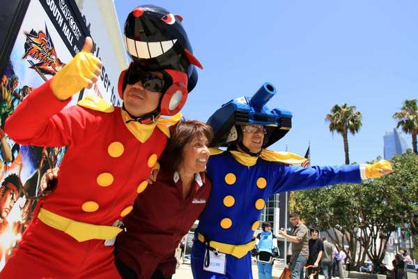 Alexis Bujosa, center, poses with two characters from the Wii U game Tank Tank Tank during E3 at the Los Angeles Convention Center.