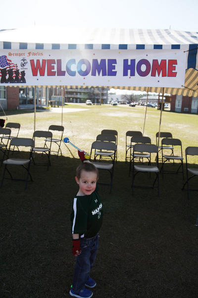 Isaac Kelber poses with the welcome home sign while waiting for his father, Sgt. Judah Kelber, to arrive at Camp Lejeune, N.C., from a seven-month deployment in Afghanistan.