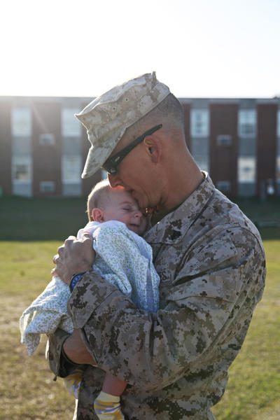 Sgt. Judah Kelber, just off the bus at Camp Lejeune, N.C., snuggles his son Aaron, just shy of 10 weeks old, for the first time after returning from a seven-month deployment to Afghanistan.