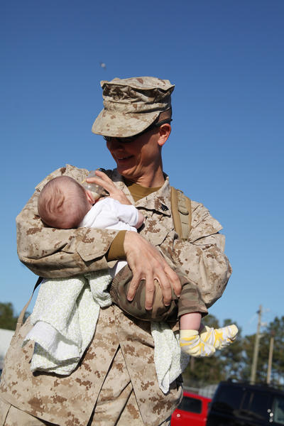Sgt. Judah Kelber, just off the bus at Camp Lejeune, N.C., feeds his son Aaron, just shy of 10 weeks old, a bottle just a few minutes after returning from a seven-month deployment to Afghanistan.