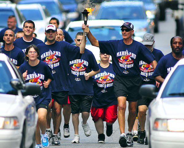 Runners in the Law Enforcement Torch Run for Special Olympics descend upon West Washington Street Wednesday. Alan Artz II is carrying the Flame of Hope torch with his father, Alan Artz.
