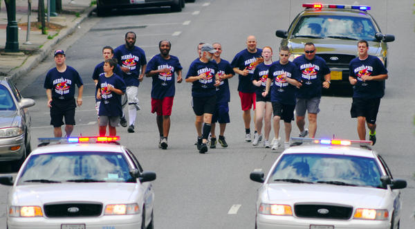 Runners in the Law Enforcement Torch Run® for Special Olympics jog on East Washington Street Wednesday. The Flame of Hope torch was lit as runners carried it toward Public Square.