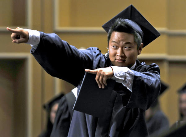 Graduate Lucas Tae Hoon Kim signals back to his family and friends during the Seventy-Ninth Flintridge Preparatory School Commencement Ceremonies held at the Pasadena Civic Auditorium, Sunday, June 3, 2012
