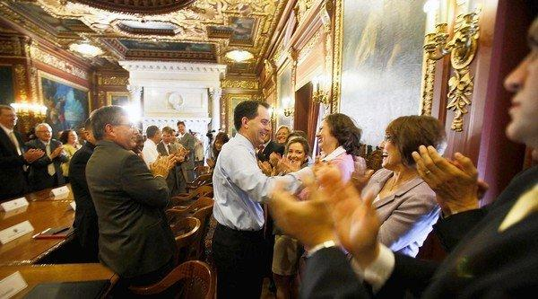 Wisconsin Gov. Scott Walker's Cabinet and staff greet him at the state Capitol the day after the Republican's victory in a recall election.