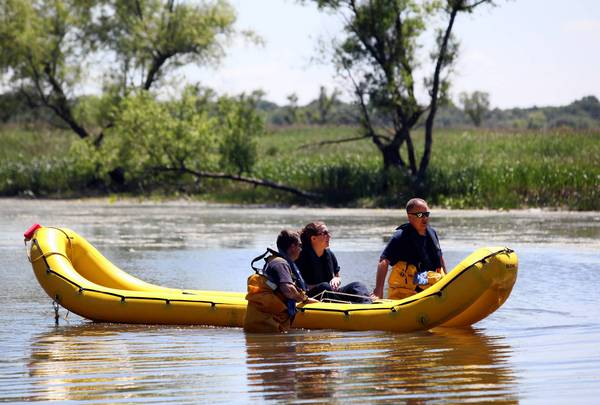 Members of a multiagency sonar team search for evidence Wednesday in the Des Plaines River near the unincorporated Lake County home of Harry Dahms. Dahms was found shot to death Friday in the gravel driveway of his home in the 14000 block of Russell Road. Investigators are still collecting evidence and speaking with residents about the homicide.