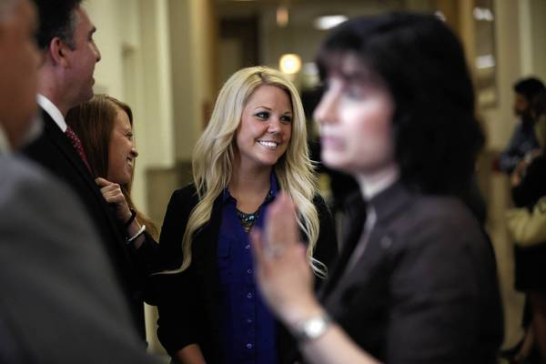 Katrina Polansky, 24, center, who suffered from a melanoma on her face from using tanning beds, was on hand Wednesday with Ald. Debra Silverstein, foreground, when a measure banning the use of tanning beds in salons for those younger than 18 was passed by the City Council.