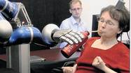 Using just her thoughts, a 58-year-old paralyzed woman instructed a robotic arm to grasp a cup of coffee and guide it to her mouth where she sipped from a straw, the first drink she has been able to serve herself in 15 years.