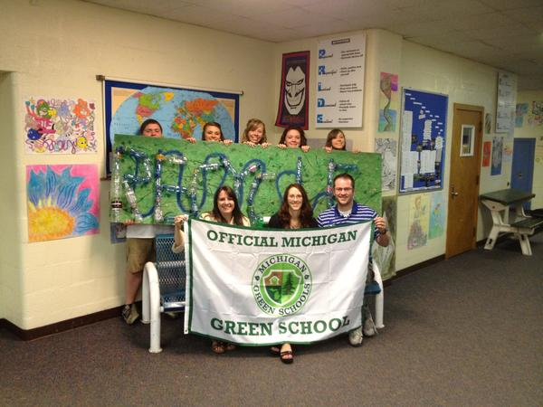 "Inland Lakes students (back row) proudly display the ""Green Schools"" banner with (front row, from left) Maureen Stine, area coordinator of Michigan Green Schools, and Inland Lakes teachers Rebecca Heckman and Nathan Jacques."