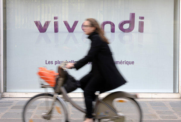 A bicyclist passes Vivendi's headquarters in Paris.