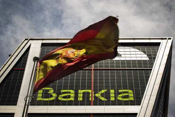 A Spanish flag flies in front of Bankia's headquarters in Madrid. Fitch slashed Spain's rating three notches Thursday.