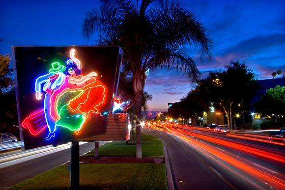 "Neon artwork stands along Santa Monica Boulevard presented by West Hollywood in collaboration with the Museum of Neon Art. The work is a part of four neon displays called ""On Route — 66 Lights."" Along this street, you'll find nightclubs and restaurants with names such as FUBAR and Mother Lode"