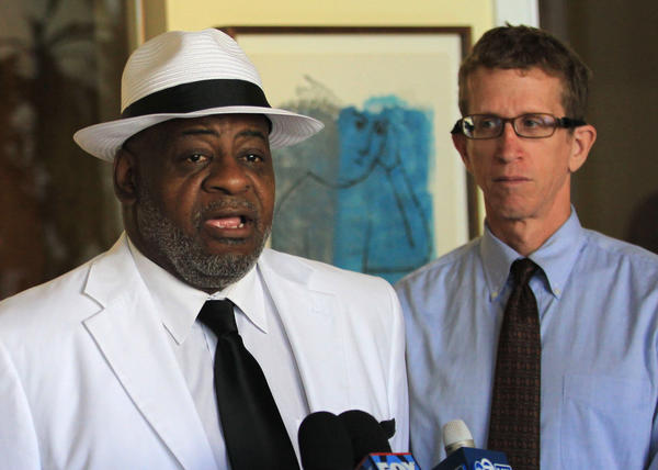 Marcus Lyons, wrongfully imprisoned for rape, speaks at a press conference today after his attorneys reached a $5 million agreement with the Village of Woodbridge for his incarceration. At right is one of his attorneys, Jon Loevy.