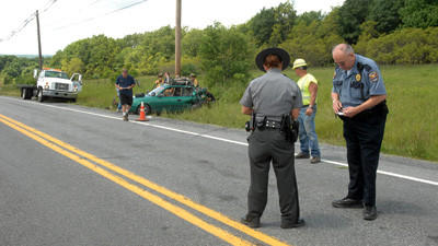 State Trooper Loni Nist and Shade Central City Chief of Police Tom Holland investigate the scene of an accident on State Route 30 near Reals Corner