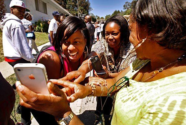 Wanda Jackson, left, and Lene Reynolds, center, scream with delight as their friend Michelle Burks, right, shows them video she took on her phone of President Obama as he drove past the crowd of more than 100 neighbors who gathered to get a view of the chief executive.