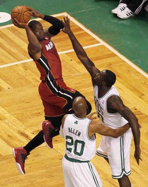 Miami Heat's Dwyane Wade (L) looks to pass as he is guarded by Boston Celtics' Brandon Bass (R) and Ray Allen during the first quarter in Game 6 of their Eastern Conference Finals NBA basketball playoffs in Boston, Massachusetts June 7, 2012.