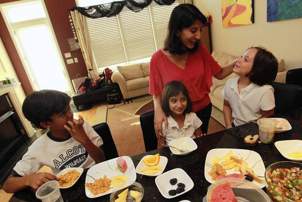 Dr. Ruchi Gupta, rear, oversees while her children and a friend have an afternoon snack. Gupta's daughter has food allergies; her son does not.