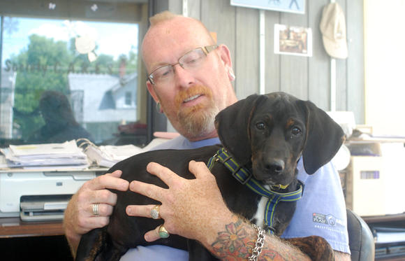 Mark Hurte, executive director of the Central Kentucky Regional Humane Society, holds Moses, an 8-month-old dog who continues to nip and play. The shelter, which has a no-kill policy, is hoping to raise enough money to build a fence around the property.