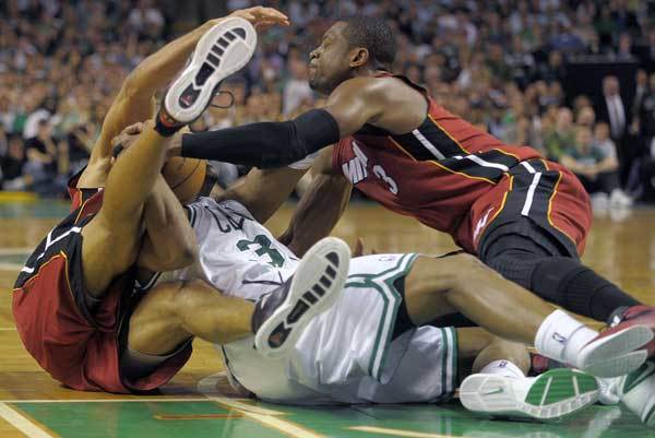 Miami Heat's Dwyane Wade and Shane Battier battle Boston Celtic forward Paul Pierce for a loose ball during the fourth quarter of Game 6 against the Boston Celtics, Thursday, June 7, 2012, at TD Garden.