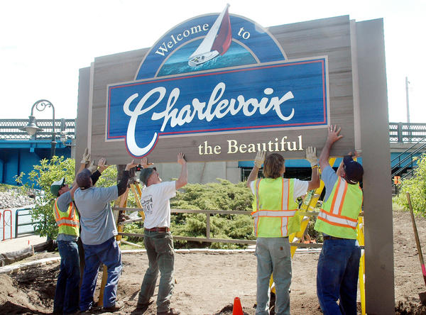 City of Charlevoix crews lift a new welcome sign into place Wednesday on the south shore of the Pine River Channel. Jonathon Lindfors, the Boy Scout who spearheaded the project for his Eagle Scout project is behind the sign starting to fasten it into place.