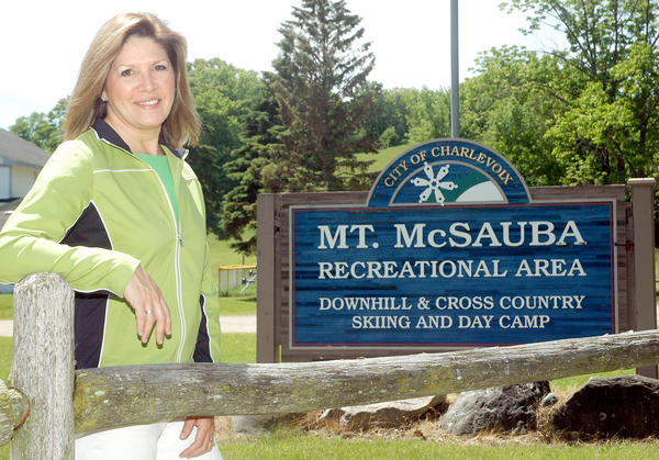 Linda Amstutz, the new director for the City of Charlevoix's Camp McSauba, stands near the Mount McSauba sign where day camps will take place again this summer