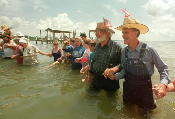 Former state senator Bernie Fowler, right, wade in the Patuxent River in 1992, just four years after he began the annual ritual to demonstrate concern for cleaning up the Chesapeake Bay. On his right is folk singer and bay advocate Tom Wisner, who died in 2010.