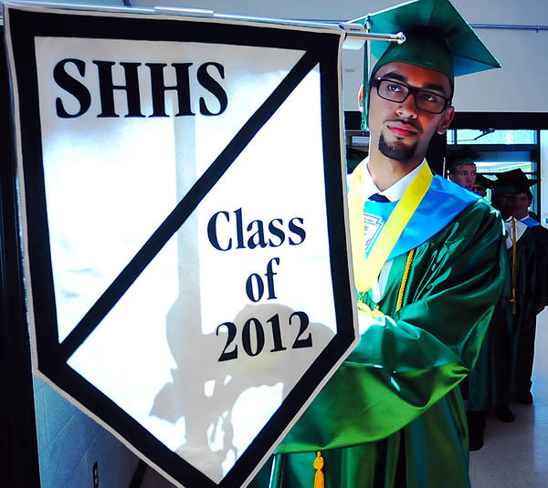 South Hagerstown High School Senior Salutatorian Umar Mahmood readies the class banner upon entering the gym for Friday's commmencement.