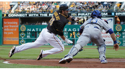 Pittsburgh Pirates' Rod Barajas, left, dives for home plate while trying to avoid the tag from Kansas City Royals catcher Humberto Quintero (33) as he scores from second on a hit by Clint Barmes in the second inning on Friday.