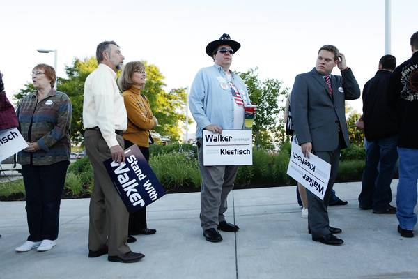 Supporters of Wisconsin Gov. Scott Walker line up ahead of a rally for him Tuesday in Waukesha.