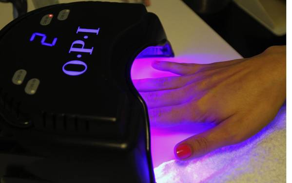 Nails dry under LED light for 30 seconds after top coat during an OPI gel manicure.