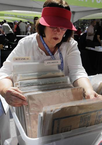 Barbara Clifford of Mill-Cliff Books organizes posters at Printers Row Lit Fest.