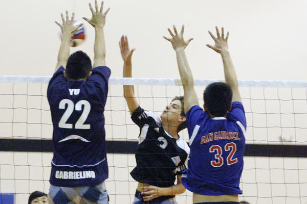 St. Francis' Charles McCarthy, center, spikes the ball during a volleyball match against public schools, which took place at Caltech in Pasadena on Saturday, June 9, 2012.