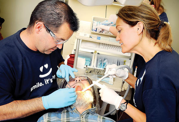 Doctors Chip Bachtell, left, and Rebecca Bye, right, work on patient Giorgio Capone, center, Saturday afternoon at Hagerstown Smiles Dental Care's Dentistry from the Heart event. Capone was having a tooth filled.