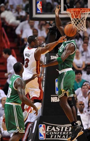 Miami Heat shooting guard Dwyane Wade (3) passes the ball between Boston Celtics power forward Kevin Garnett (5) and  Brandon Bass (30) during the first quarter in game seven of the 2012 NBA Eastern Conference finals at the American Airlines Arena.