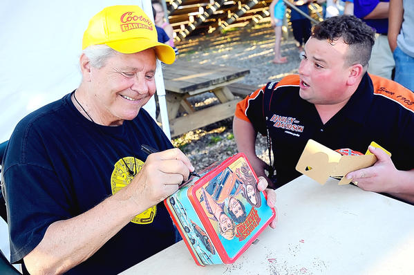 "Ben ""Cooter"" Jones,  left, signs an original ""Dukes of Hazzard"" lunchbox for Waynesboro, Pa., resident Rick Baker, right, Saturday night at the Hagerstown Speedway."