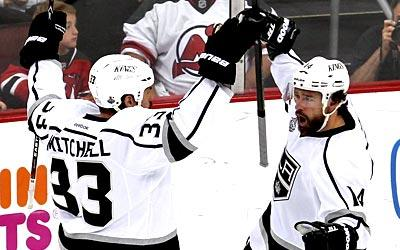 The Kings' Justin Williams celebrates his second-period goal with teammate Willie Mitchell.