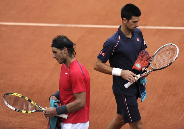 Rafael Nadal passes by Novak Djokovic during their Men's Singles final tennis match of the French Open tennis tournament at the Roland Garros stadium, on June 10.