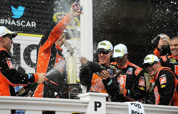Joey Logano, driver of the #20 Home Depot Toyota along with his crew begin to celebrate their victory at the 31st Annual Pocono 400 at Pocono Raceway Sunday afternoon.