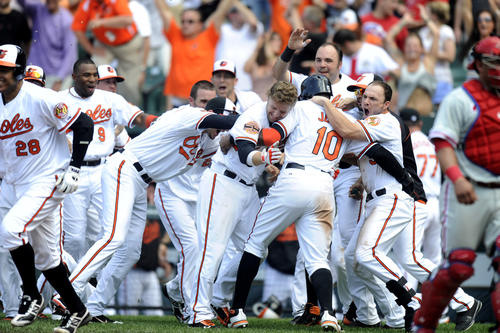 Adam Jones celebrates with his Orioles teammates after scoring the game-winning run against the Phillies on an RBI double by Matt Wieters in the 10th inning of the O's 5-4 victory.