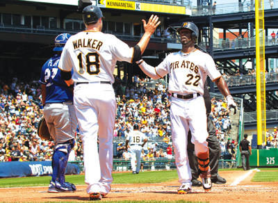Pittsburgh Pirates' Andrew McCutchen (22) is greeted at home plate by Neil Walker after hitting a two-run home run in the third inning against the Kansas City Royals on Sunday.